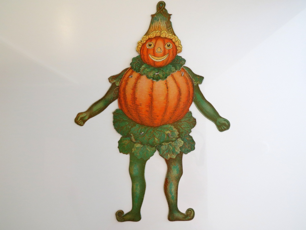 "Hallowe'en Elf.  This richly detailed mechanical decoration was issued by Beistle between 1923 and 1932. The elf was designed to be part of a male and female couple. The male iteration (shown) is denoted by the presence of an additional layer of foliage beneath his abdomen. The female iteration (not shown) is denoted by the presence of only one layer of foliage beneath her abdomen as well as being smaller in size than her male counterpart. Measures 21"" h x 18.25"" w with arms fully extended. This high-quality top-shelf example is in immaculate condition."