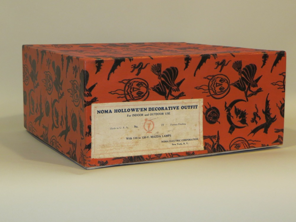 "Hollowe'en Decorative Outfit No.77, USA, NOMA Electric Corporation, made for only two seasons: 1930 - 1932, seven celluloid JOLs: six measuring 4"" in diameter and one (center) measuring 6"" in diameter. The original deep and quite large decorative box with lift-off lid measures: 6"" h x 13.25"" square."