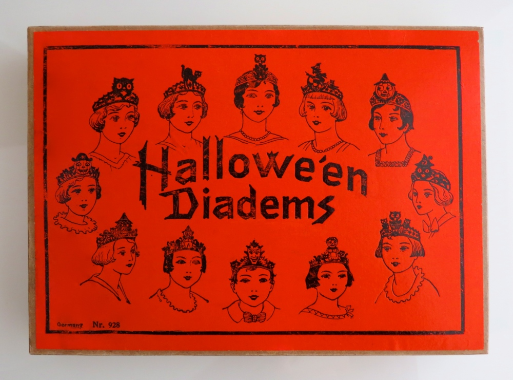 "Boxed set of twelve heavily embossed Hallowe'en Diadems (tiaras), Germany, 1920s. Box: 7"" h x 1.5"" w x 10.5"" l. Each design is depicted on the box top. A stock number, 928, is printed at lower left. All twelve tiaras are original to this set, complete with thin elastic strings intact. This uber-rare, high-quality example is in immaculate condition."